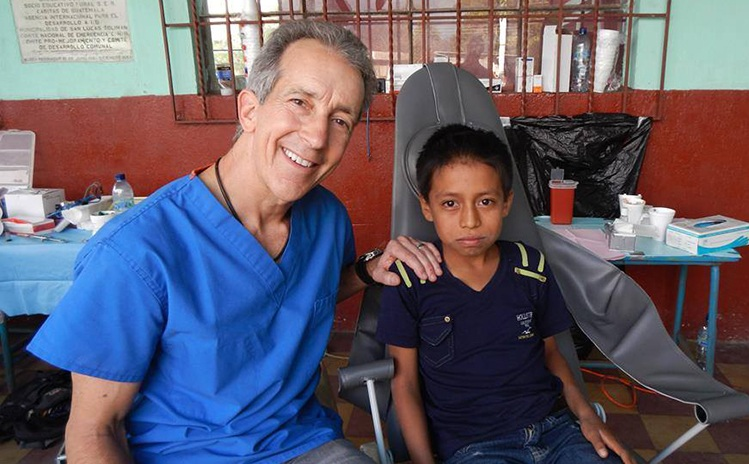 Dentist and child posing on mission trip