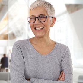 gray-haired woman smiling with dental implants in Mesquite