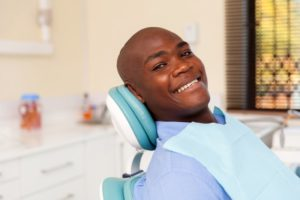 young man dental chair smiling