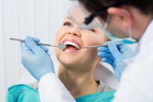 woman smiling receiving dental checkup