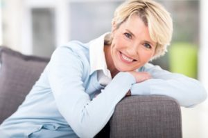 Woman leaning on the arm of a couch smiling
